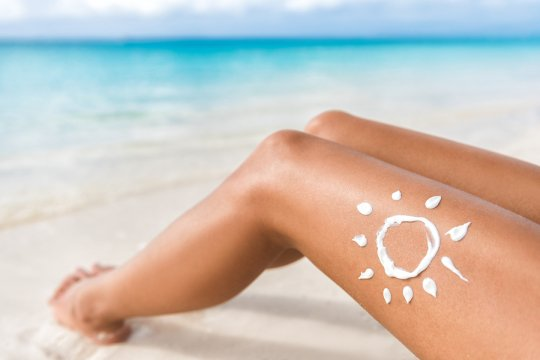 woman with sunscreen on leg in the shape of a sun