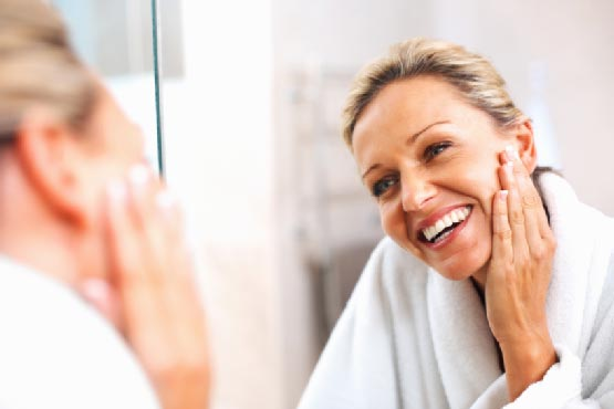 woman smiling at her reflection in mirror