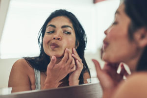 woman inspecting pimple in mirror