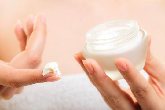 woman using skin care cream