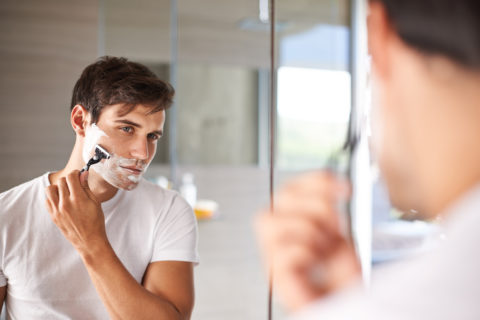 man shaving and looking into mirror